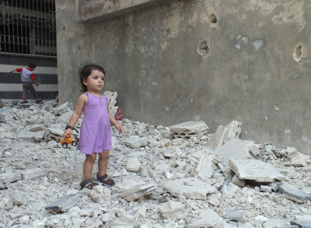 A girl stands on debris in Homs, Syria (Reuters, Yazen Homsy)